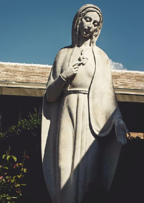 A statue of Mother Mary in a garden.